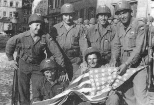 Kitzingen, Germany, May 1945. 1st Lt Samuel Lombardo and platoon members displaying the flag for a US Army photograph. Back Row: L to R: Pfc. Gordon Wetherby, Charlestown, NH; T/Sgt Isadore Rosen, Pittsburgh, PA; Pfc. George E. Bellaire, Dayton, OH; 1st Lt. Samuel Lombardo, Altoona, PA Front Row: Left to Right: Corp. Cury Beauvais, Chicopee Falls, MA; S/Sgt William Junod, Wyandotte, MI