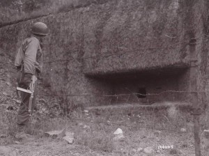 Signal Corps photograph of a GI inspecting a captured concrete pillbox.